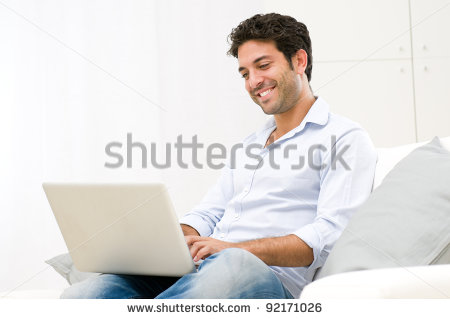 stock-photo-happy-smiling-young-man-watching-and-working-on-computer-laptop-at-home-92171026